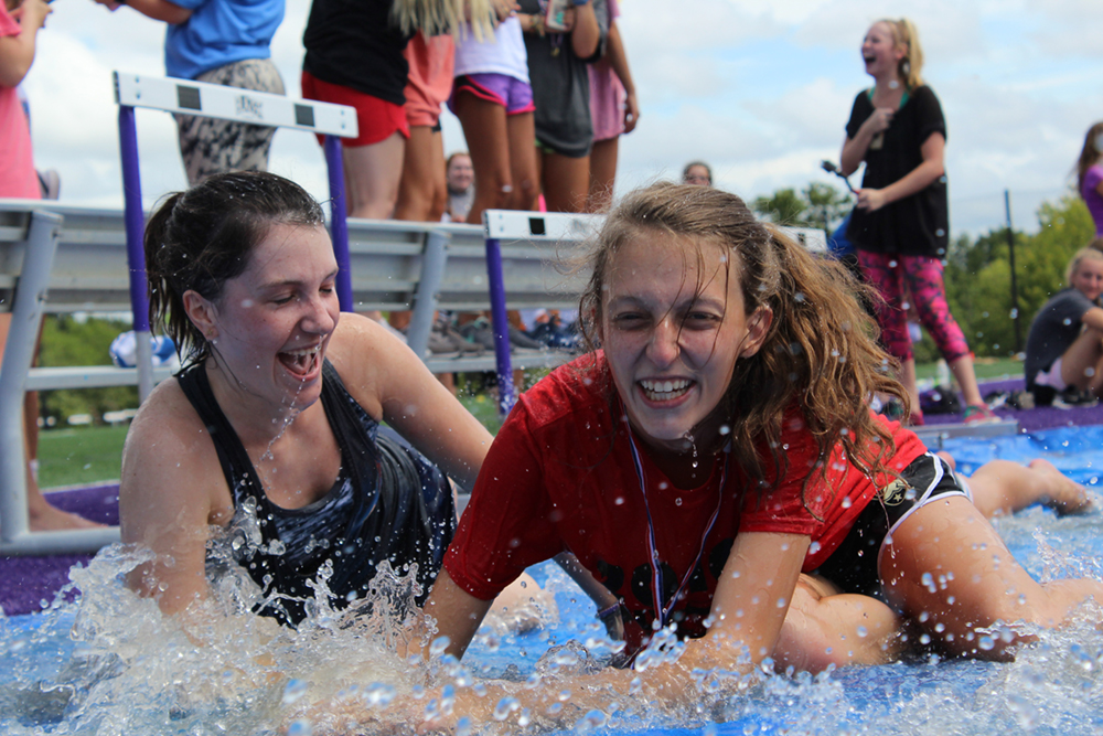 During a break in Freshmen Field Day, seniors Bridget Koeppen and Abby Englert slide into rainwater left on a tarp covering the long jump sand pit. An annual back to school tradition, freshman and seniors participated in a variety of activites, including Pound, tug of war and chalk drawing.