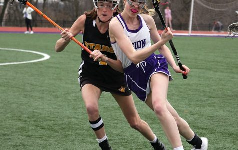 As sophomore attackman Delaney Minor carries the ball down the field, she gets up close and personal against St. Teresa's Academy's (STA) senior Rose Crowe April 4. Despite the home field advantage, the lacrosse team fell to STA 5-15.