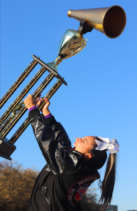 """As the sun sets on the Fort Worth city skyline senior Bella Aquino hoists the national championship trophy above her head March 7. The cheer team placed first in their national competition, the only competition they got to compete in due to the cancellation of Regionals to qualify for State. """"It made me feel like I was on top of the world,"""" Aquino said. """"All of Coach Tabby"""